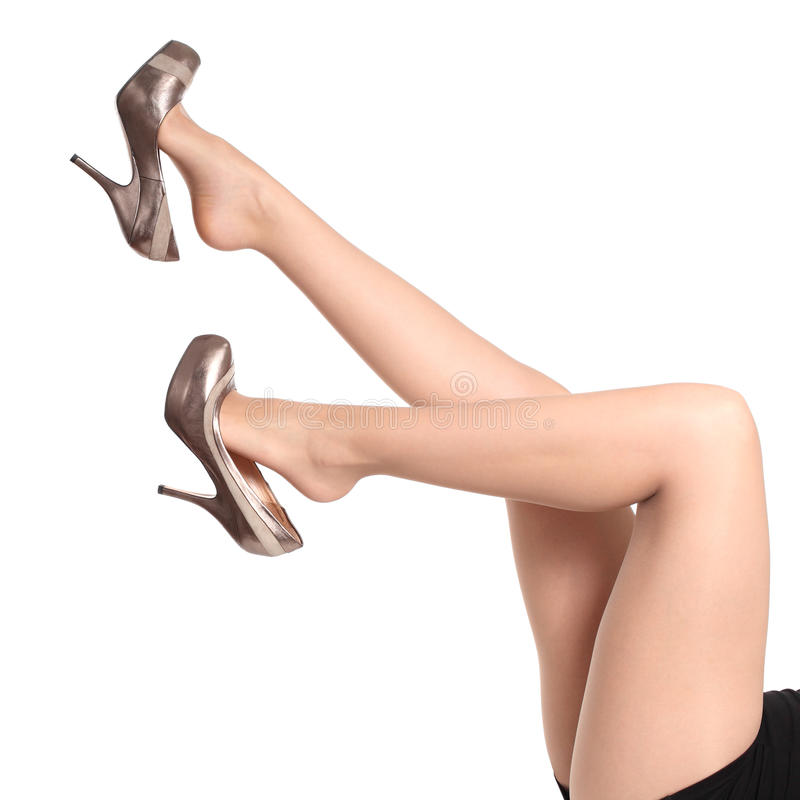 Den härliga kvinnan lägger benen på ryggen upp med strumpbyxor och att dingla för häl arkivbilder
