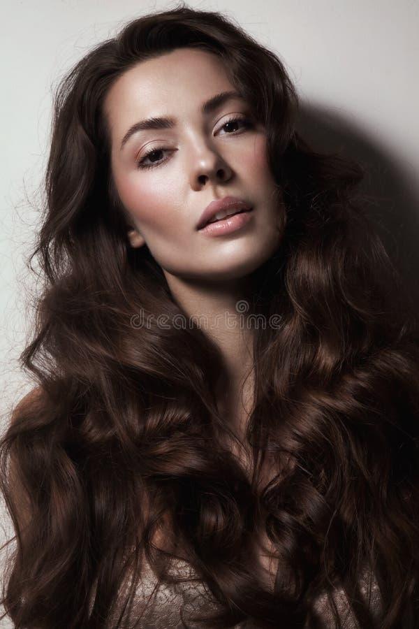 Den härliga sexiga kvinnan med långt lockigt hår och rengöringen gör-u royaltyfria bilder