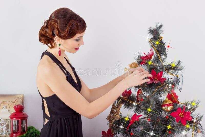 Den härliga sexiga lyckliga le unga kvinnan i aftonklänning med ljus makeup med röd läppstift, dekorerar en julgran arkivfoton