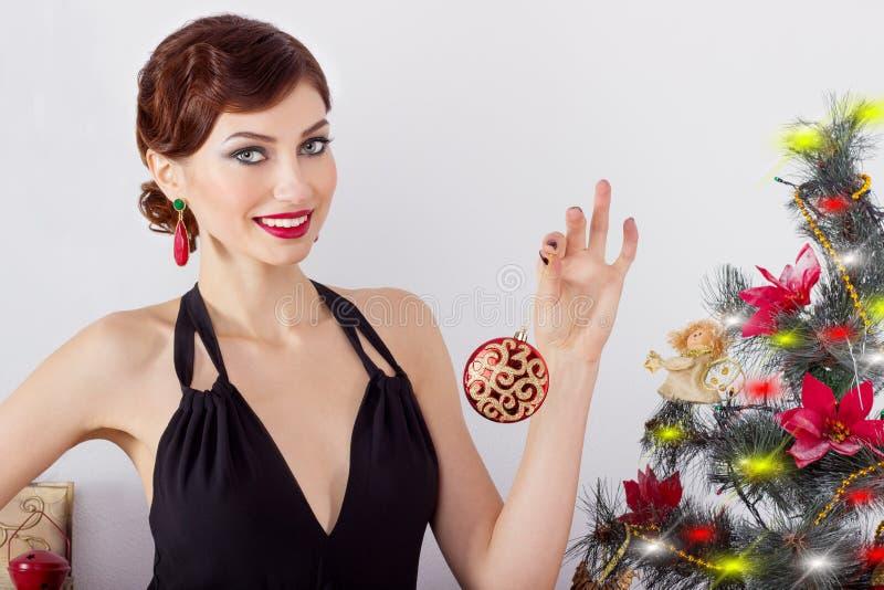 Den härliga sexiga lyckliga le unga kvinnan i aftonklänning med ljus makeup med röd läppstift, dekorerar en julgran royaltyfria bilder