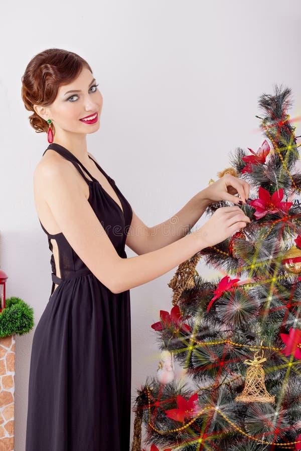 Den härliga sexiga lyckliga le unga kvinnan i aftonklänning med ljus makeup med röd läppstift, dekorerar en julgran royaltyfri fotografi