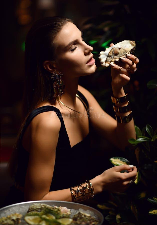 Den härliga sexiga modebrunettkvinnan i dyr inre restaurang äter ostron royaltyfri fotografi