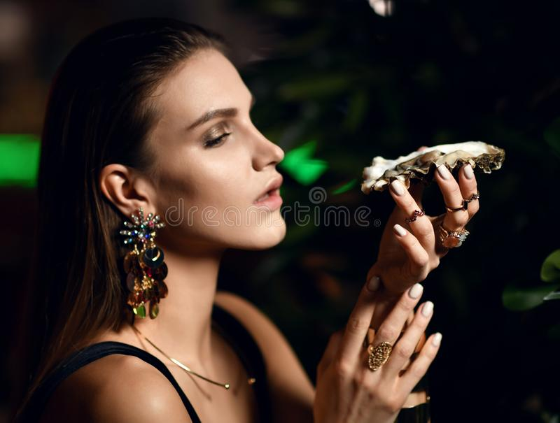 Den härliga sexiga modebrunettkvinnan i dyr inre restaurang äter ostron arkivfoto