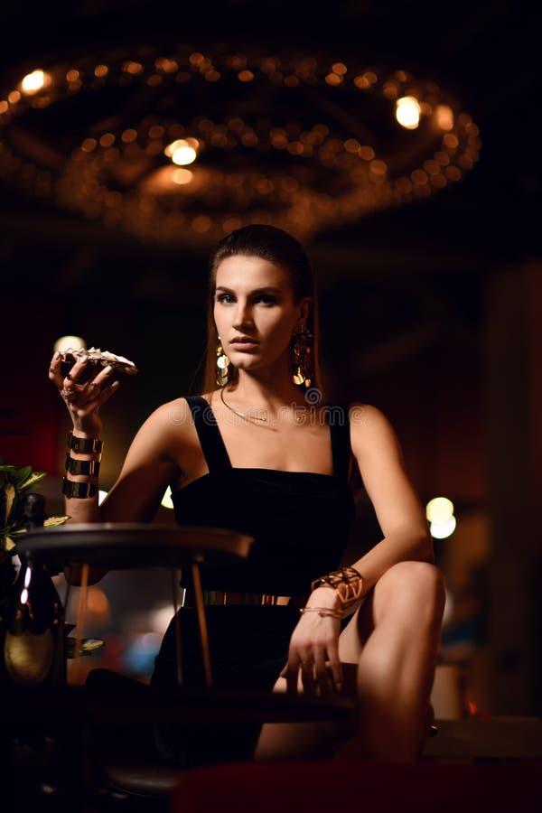 Den härliga sexiga modebrunettkvinnan i dyr inre restaurang äter ostron royaltyfri bild