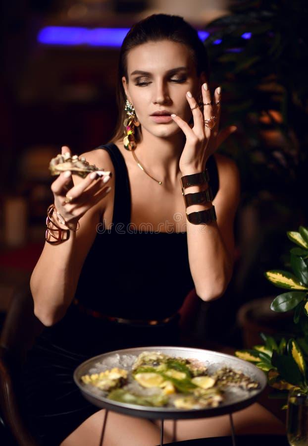 Den härliga sexiga modebrunettkvinnan i dyr inre restaurang äter ostron arkivbild