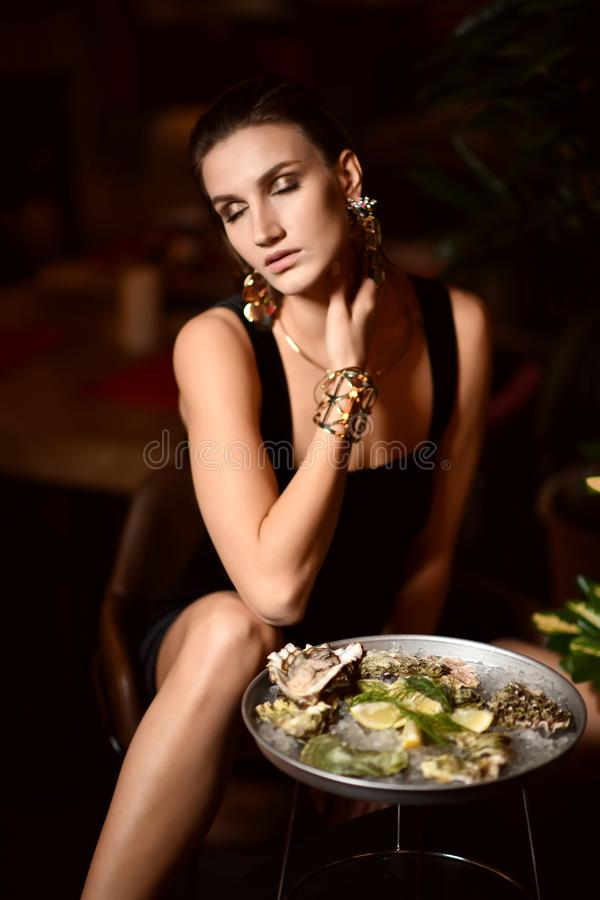 Den härliga sexiga modebrunettkvinnan i dyr inre restaurang äter ostron arkivbilder