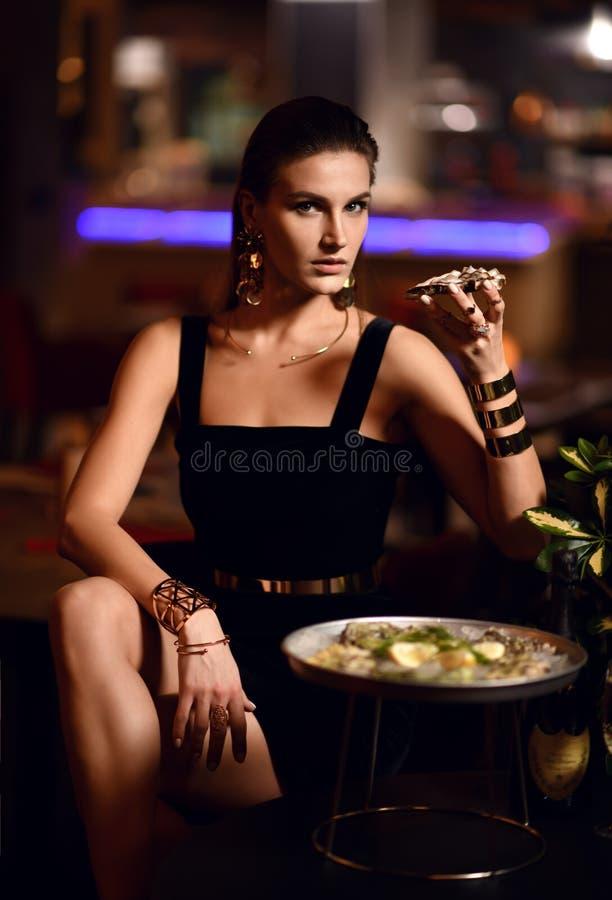 Den härliga sexiga modebrunettkvinnan i dyr inre restaurang äter ostron royaltyfri foto