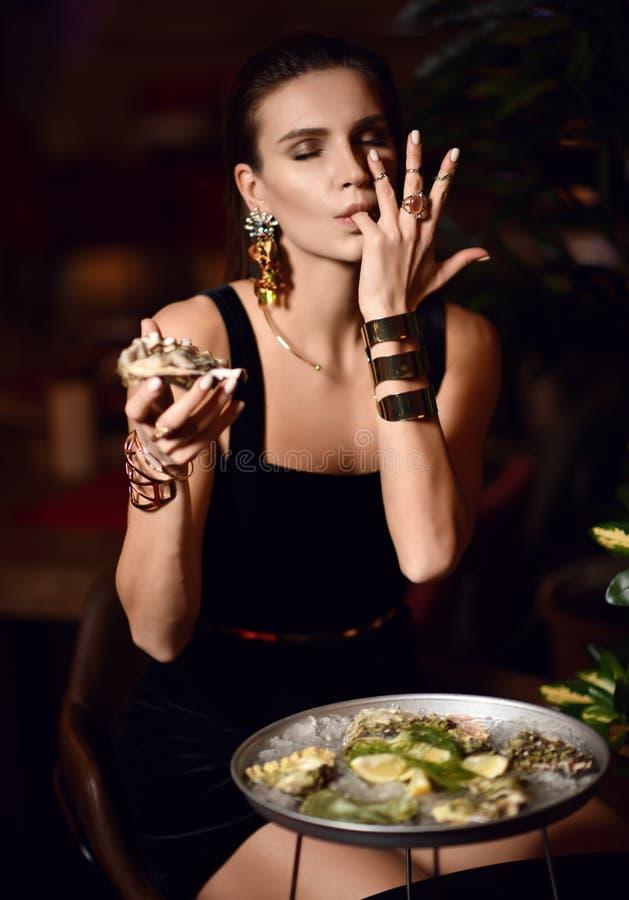Den härliga sexiga modebrunettkvinnan i dyr inre restaurang äter ostron och slickar ett finger arkivfoton