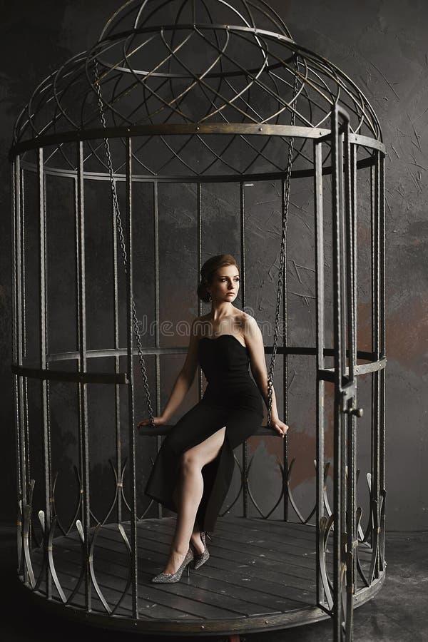 Den härliga, sexiga och trendiga brunettmodellflickan i lång svart klänning och ljusa silverskor sitter på en hängande gunga och  royaltyfri fotografi