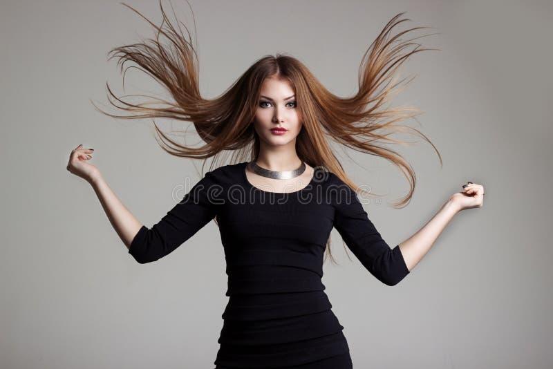 Den härliga sexiga unga kvinnan i en svart klänning med ljus makeup kastar rött hår royaltyfri bild