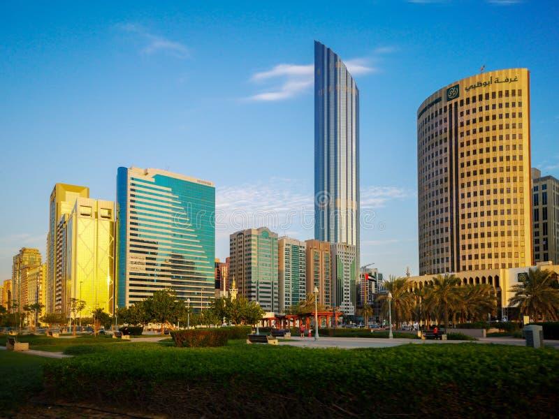 Den härliga sikten av den Abu Dhabi staden står högt, byggnader och parkerar på solnedgången från cornichen royaltyfria bilder