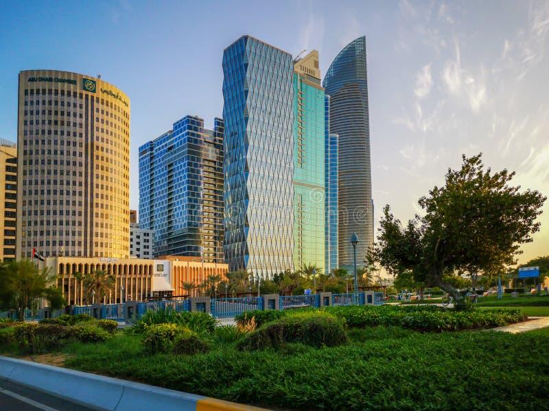 Den härliga sikten av den Abu Dhabi staden står högt, byggnader och parkerar på solnedgången från cornichen royaltyfria foton
