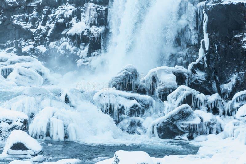 den härliga sikten av den sceniska vattenfallet, den fryste floden och snö-täckt vaggar i thingvellirmedborgare royaltyfri bild