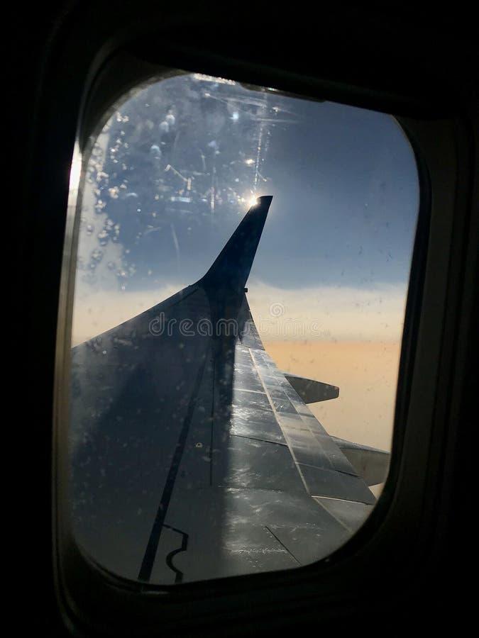 Den härliga sikten från flygplanfönster, den stora vingen av flygplan visar sidohängt fönster royaltyfria bilder
