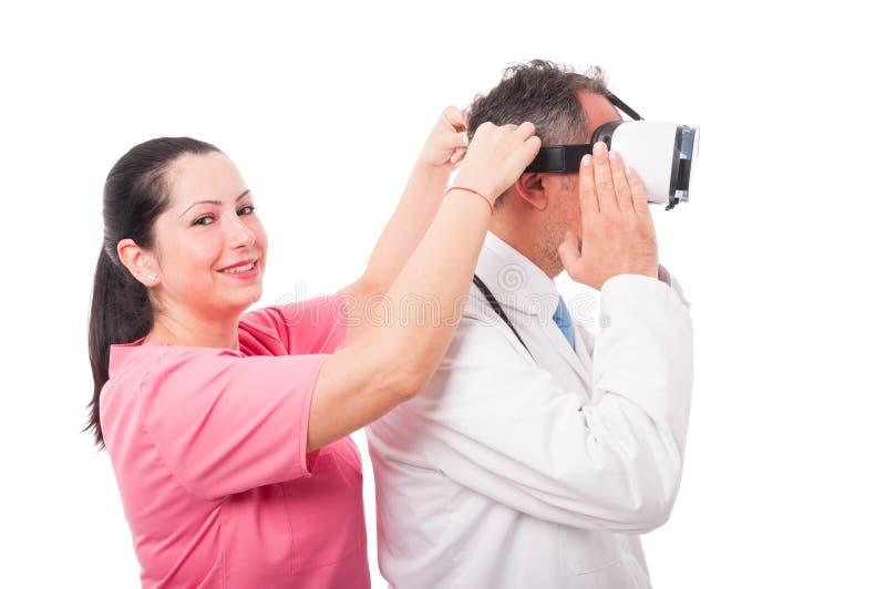 Den härliga sjuksköterskan som sätter vr, rullar med ögonen på läkarehuvudet royaltyfria bilder