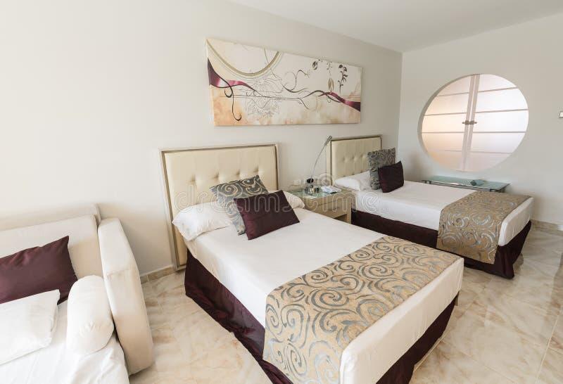 den härliga slags tvåsittssoffa, den fantastiska hotellruminre med att invitera bekvämt sova bäddar ned arkivbilder