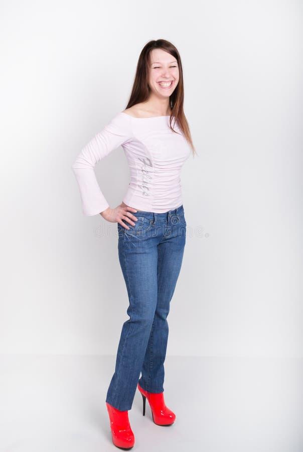 Den härliga slanka flickan i grov bomullstvill flåsar och röda hög-heeled skor och t-skjortan arkivbild