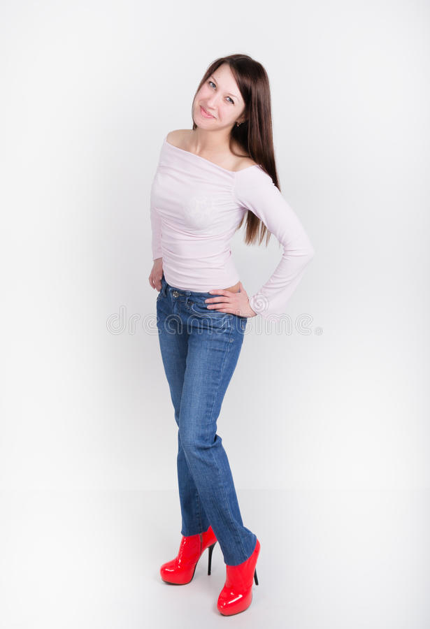 Den härliga slanka flickan i grov bomullstvill flåsar och röda hög-heeled skor och t-skjortan royaltyfri bild