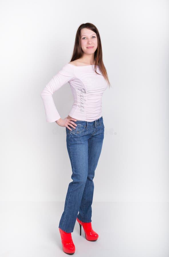 Den härliga slanka flickan i grov bomullstvill flåsar och röda hög-heeled skor och t-skjortan royaltyfria bilder