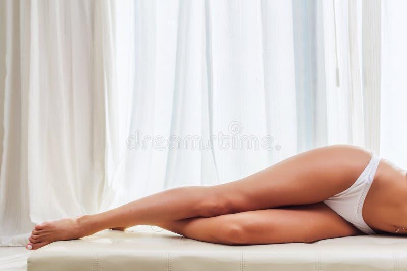 Den härliga slanka kvinnlign lägger benen på ryggen den bärande vita underkläderna som ligger på säng med det ljusa fönstret och, royaltyfri fotografi
