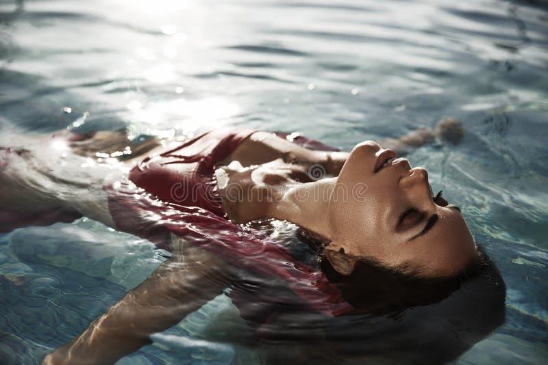 Den härliga sol-garvade kvinnan med stängda ögon i vattnet tycker om hennes semester, genom att ta, solbadar i simningröstningen arkivbild
