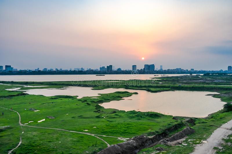 Den härliga solnedgången över Red River i Hanoi, Vietnam Cityscape fotografering för bildbyråer