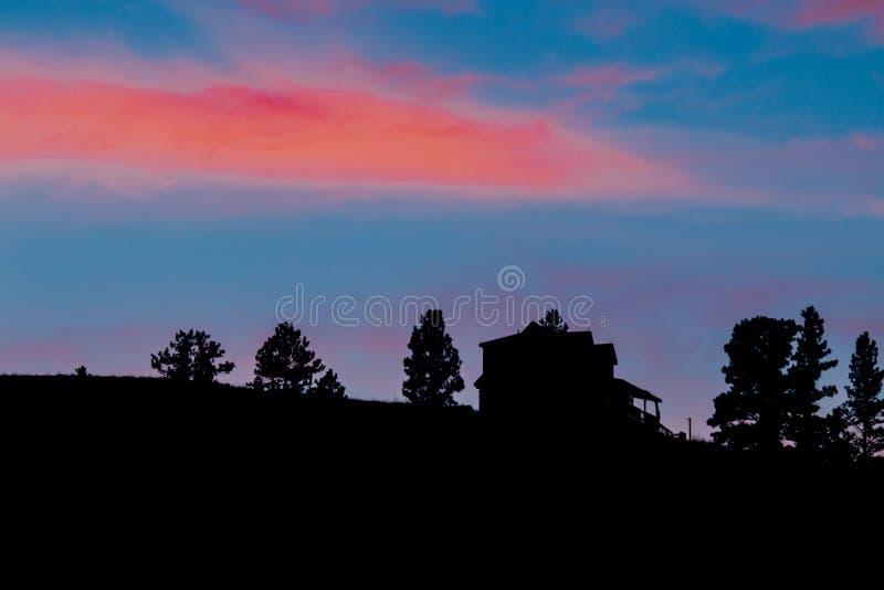Den härliga solnedgången bakom sörjer trädet och huset royaltyfria foton