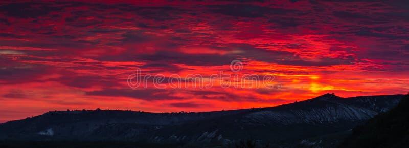 Den härliga solnedgången för HDR platsen på senare med röda himlar över gör mörkare jordning och några konturer av träd och kulla royaltyfri fotografi