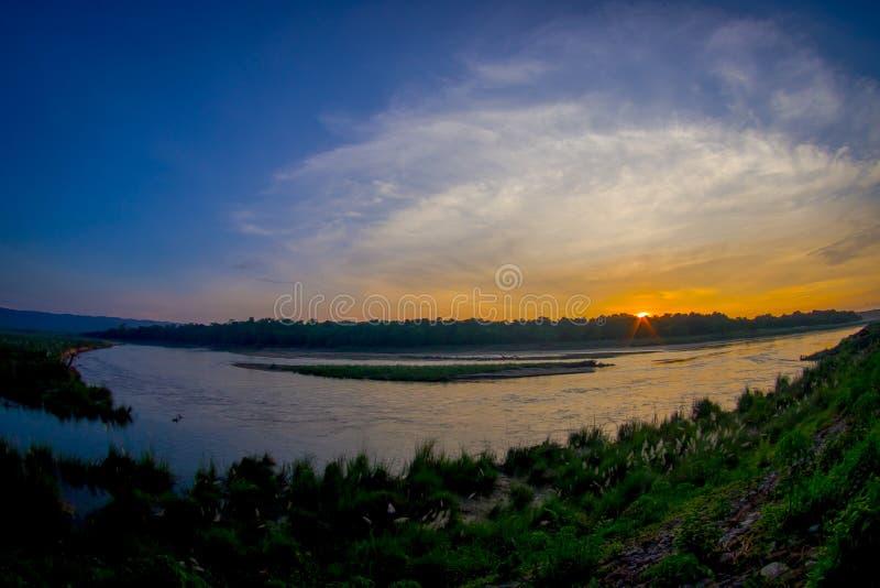 Den härliga solnedgången i den Chitwan nationalparken, täckas främst av djungeln, effekt för fisköga arkivbilder