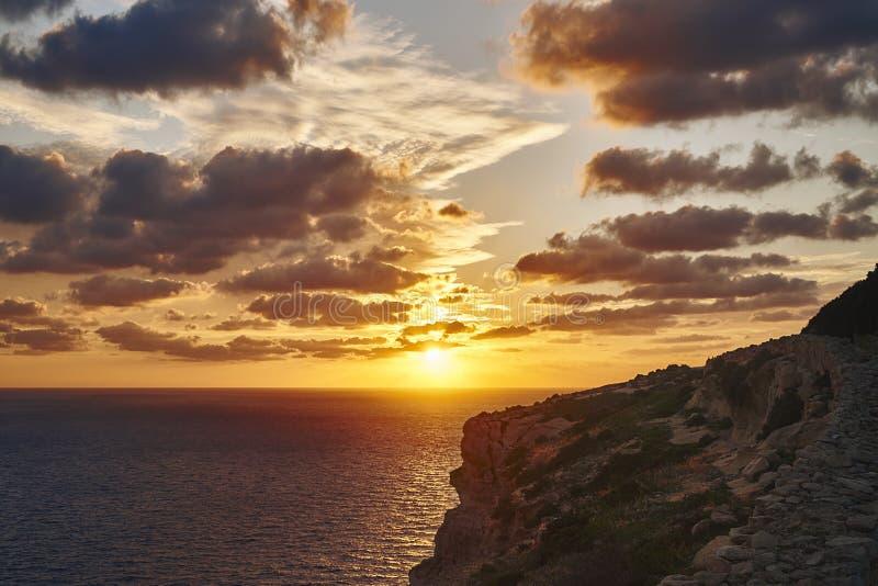 Den härliga solnedgången på bakgrunden av vaggar royaltyfria foton