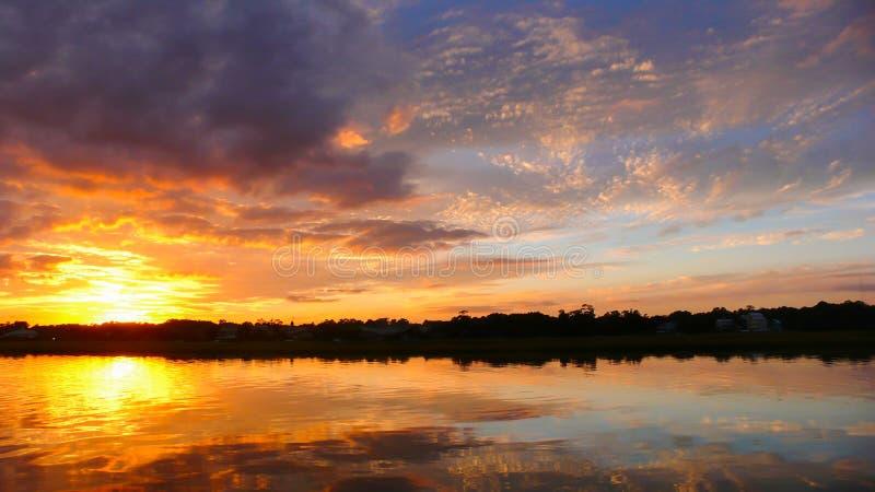 Den härliga solnedgången som ställer in över vatten, och marsklan i vattnet för barriäröcreeksiden av South Carolina seglar utmed arkivfoton