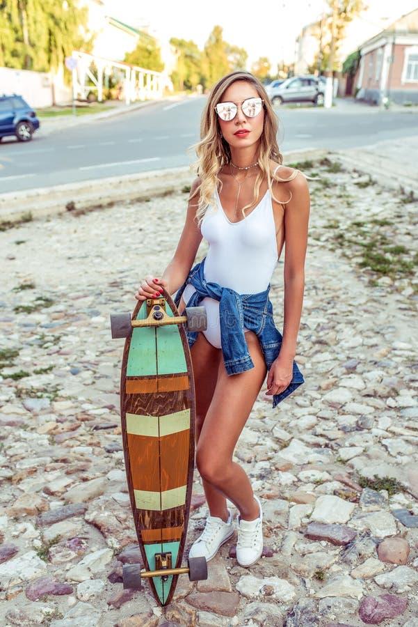 Den härliga sommarflickan i stad står, skateboardlongboarden Trendig och stilfull kvinna i en baddräktkropp arkivbilder