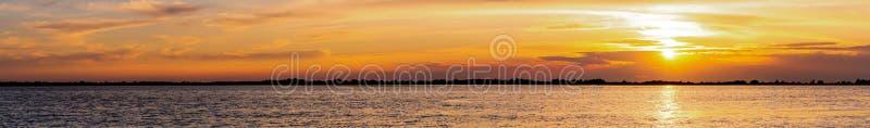 Den härliga sommarsolnedgången med solljus reflekterade i vattnet av en sjö arkivbild