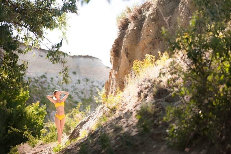 Den härliga spensliga flickan i en gul baddräkt mot bakgrunden av vaggar, en klippa i ljuset av inställningssolen fotografering för bildbyråer