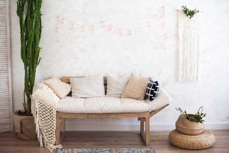 Den härliga sping dekorerade inre i texturerad vit färgar Vardagsrum, beige soffa med en filt och en stor kaktus arkivbilder
