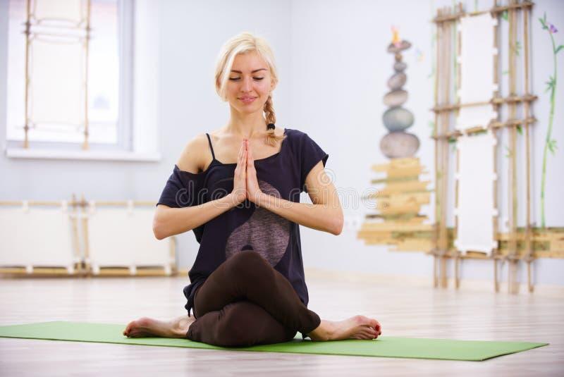 Den härliga sportiga asanaen Garudasana Eagle för yoga för övningar för passformyogikvinnan poserar i konditionrummet arkivbild