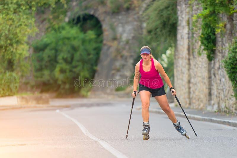 Den härliga sportiga blonda flickan med Rollerblade och klättringen klibbar arkivbild