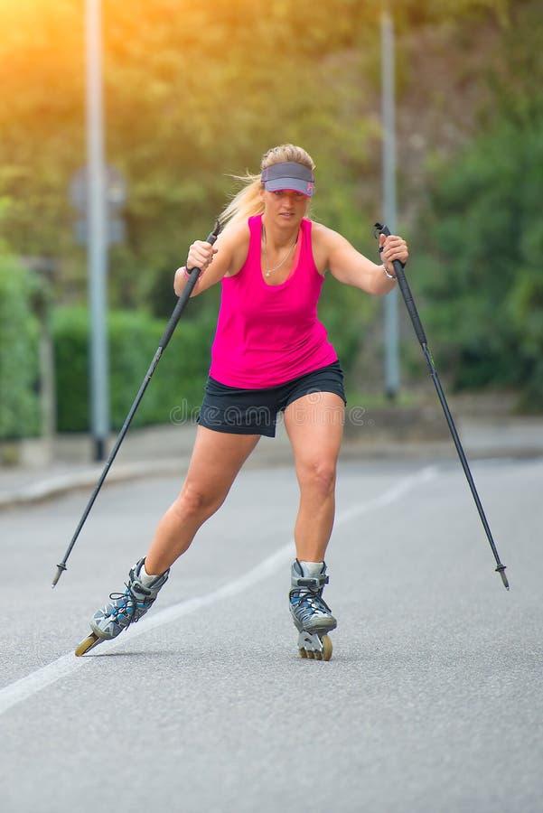 Den härliga sportiga blonda flickan med Rollerblade och klättringen klibbar royaltyfri fotografi
