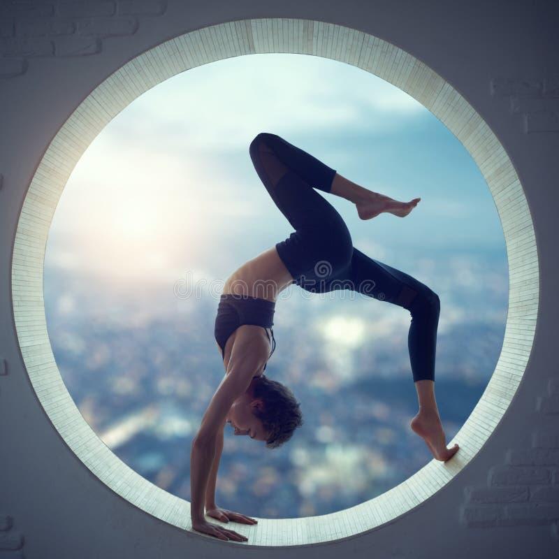 Den härliga sportiga passformyogikvinnan öva yogaasanaen Eka Pada Urdhva Dhanurasana i ett runt fönster arkivfoto