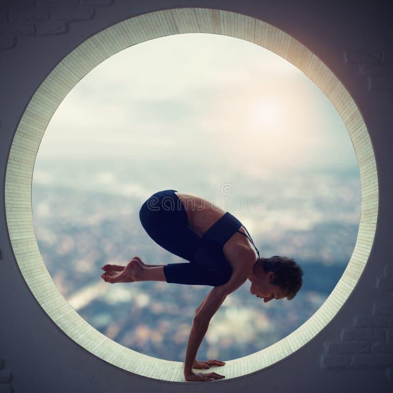 Den härliga sportiga passformyogikvinnan öva yogaasanaen Natarajasana - Lord Of The Dance poserar i ett runt fönster arkivfoto