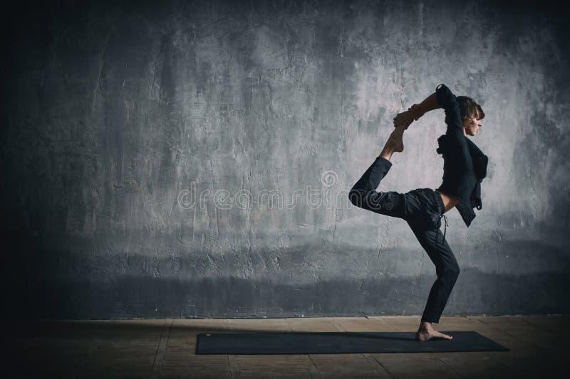 Den härliga sportiga passformyogikvinnan öva yogaasanaen Natarajasana - Lord Of The Dance poserar i den mörka korridoren royaltyfri foto