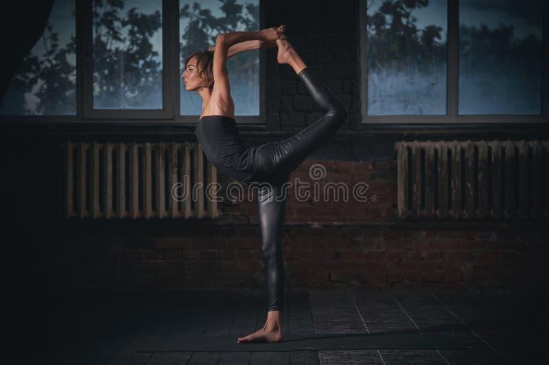 Den härliga sportiga passformyogikvinnan öva yogaasanaen Natarajasana - Lord Of The Dance poserar i den mörka korridoren royaltyfri fotografi