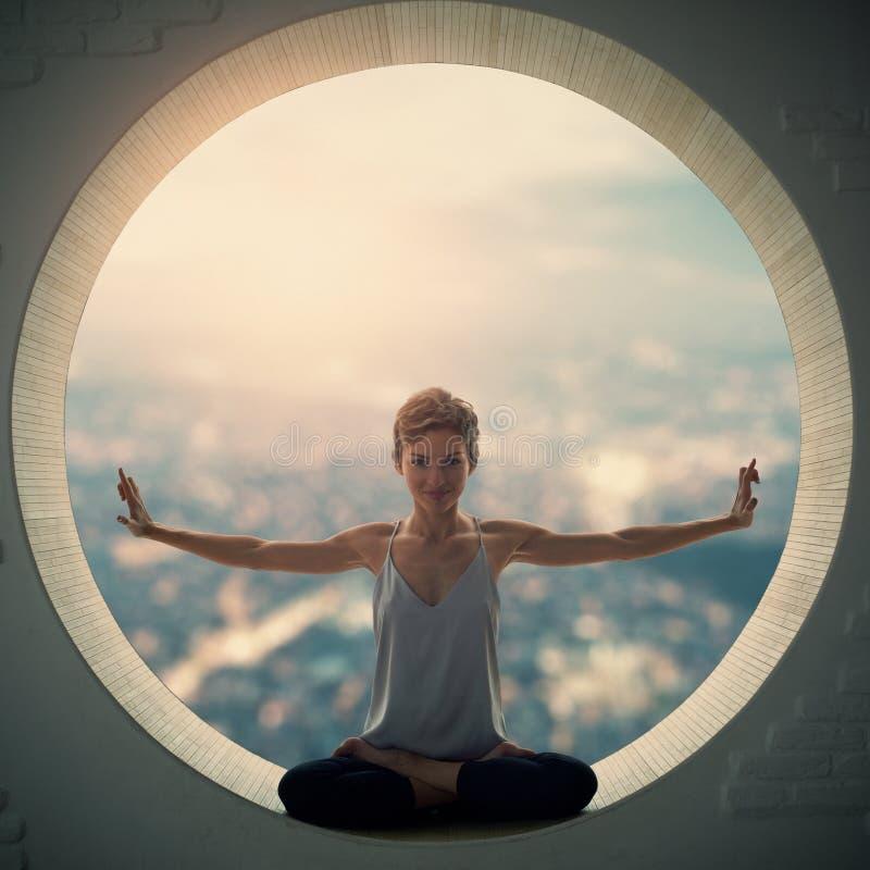 Den härliga sportiga passformyogikvinnan öva yogaasanaen Padmasana - Lotus poserar i ett runt fönster arkivfoto