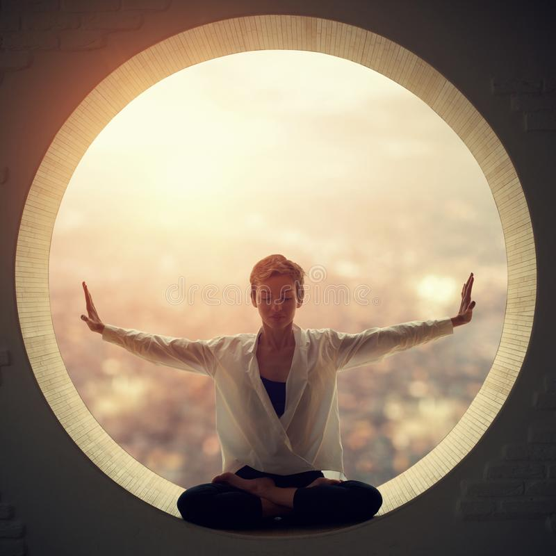 Den härliga sportiga passformyogikvinnan öva yogaasanaen Padmasana - Lotus poserar i ett runt fönster arkivbilder