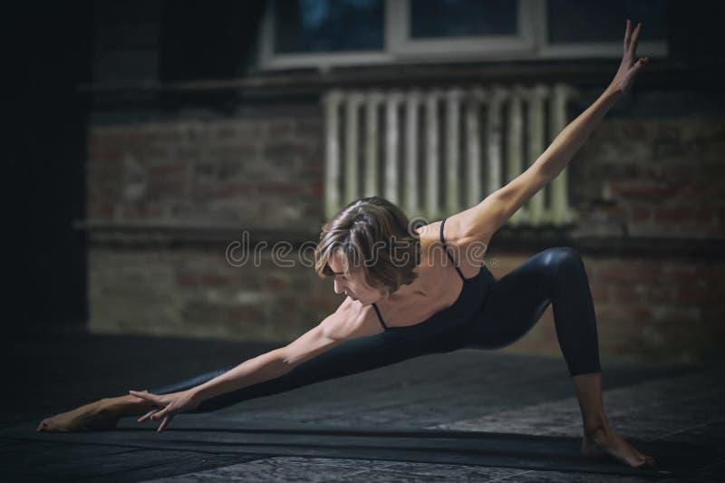 Den härliga sportiga passformyoginikvinnan öva yogaasana i den mörka korridoren royaltyfri bild