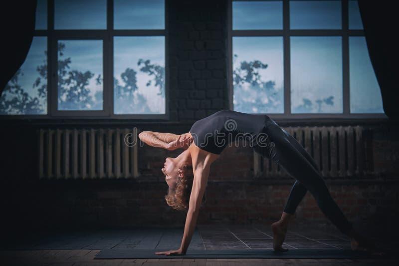 Den härliga sportiga passformyoginikvinnan öva yogaasana som det lösa tinget poserar i den mörka korridoren royaltyfria foton