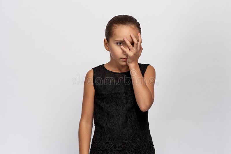 Den härliga ståenden av en uttråkad flicka, den halva framsidan stängde sig vid gömma i handflatan flickan med svart hår tröttade royaltyfri bild