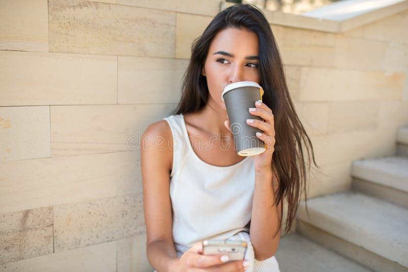 Den härliga ståenden av den unga attraktiva brunettkvinnan som dricker med en kopp kaffe eller ett te som sitter på momenten i, p royaltyfri foto