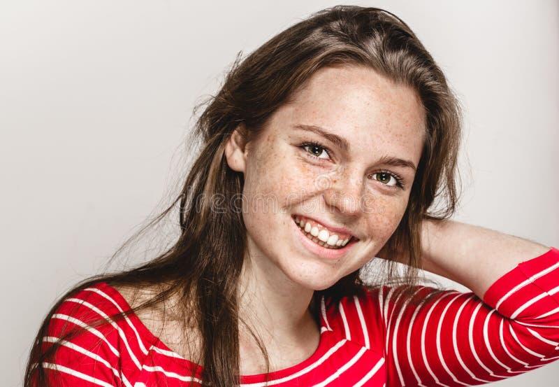 Den härliga ståenden för den unga kvinnan får fräknar att le posera attraktiv brunett arkivbild