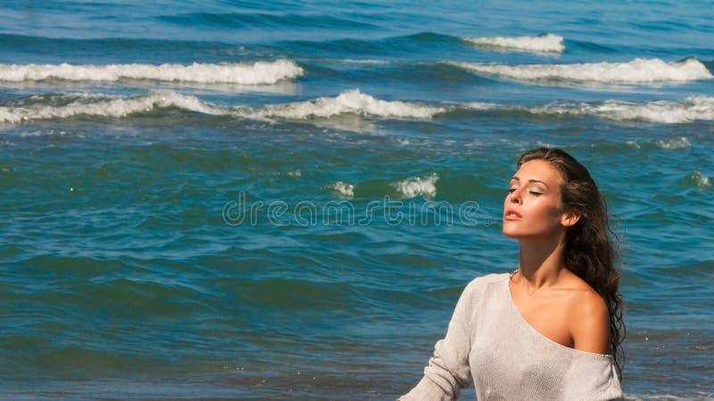 Den härliga ståenden för den unga kvinnan tycker om i sol, och havsluft på stranden stängde ögon som kopplar av sommar royaltyfri fotografi